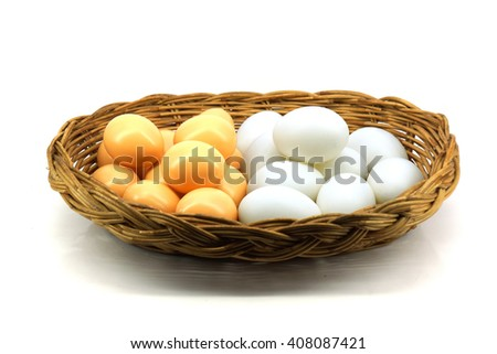Duck eggs and brown eggs in the basket isolated on white background - stock photo