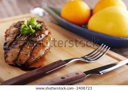 Duck fillet on wood board with fork and knife