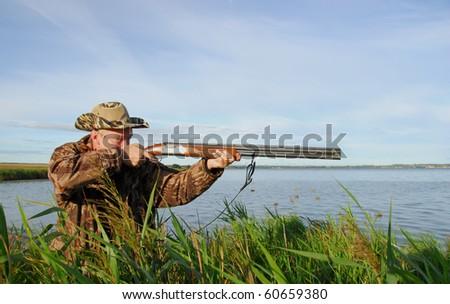 Duck hunter aims his gun - stock photo