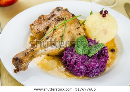 Duck leg, potato dumplings, red cabbage and gravy, close up - stock photo