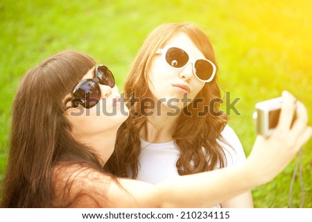 Duckface. Selfie. Two young trendy girls doing selfie. A couple of friends photographing themselves. Two women did a photo shoot in nature. - stock photo