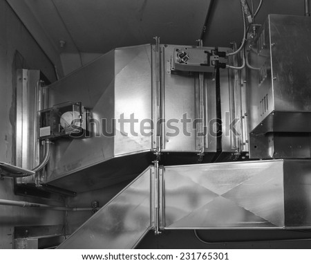 Ductwork with damper actuator controls air flow into an air conditioned space. Smoke detector in housing samples air for combustion. - stock photo