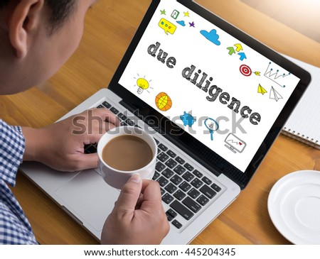 due diligence  Businessman at work. Close-up top view of man working on laptop while sitting at the wooden desk , coffee - stock photo