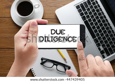due diligence  message on hand holding to touch a phone, top view, table computer coffee and book - stock photo