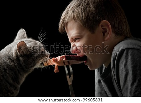 duel of predators - cat and boy on black - stock photo