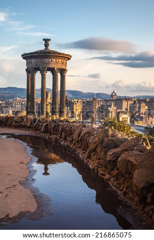Dugald Stewart monument at Calton Hill with Edinburgh (Scotland) in background. Calton Hill is popular hill in central Edinburgh included in UNESCO World Heritage Site list. - stock photo