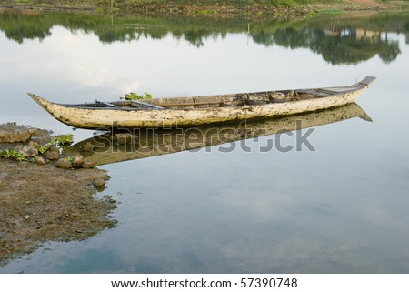 Dugout canoe on a tributary to the Mekong - stock photo