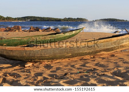 Dugout fishing canoe on the beach with coast and spray in the background in Axim, Ghana - stock photo