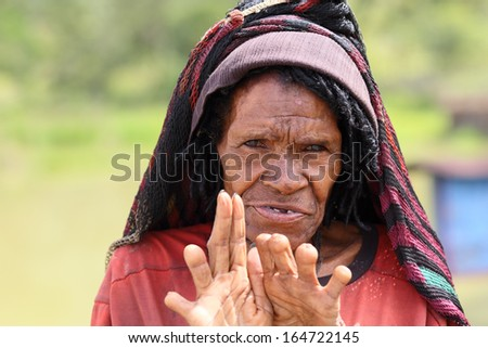 DUGUM DANI VILLAGE, BALIEM VALLEY, IRIAN JAYA, NEW GUINEA, INDONESIA - July 18, 2013  On July 18, 2013 in DUGUM Dani Village, New Guinea, Indonesia. A woman cut off her finger when a relative dies - stock photo
