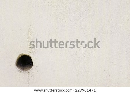 dull concrete wall with round drain hole - stock photo