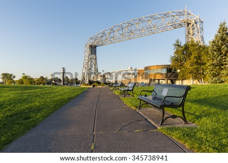 Duluth Canal Park - A sidewalk with park benches leading toward a lift bridge. - stock photo