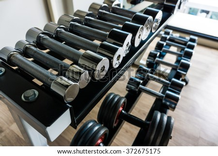 Dumb bells lined up in fitness room,  modern sports club. - stock photo