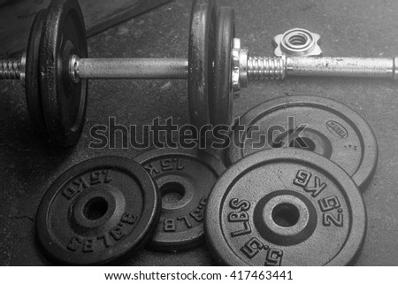 dumbbell and iron plates black and white