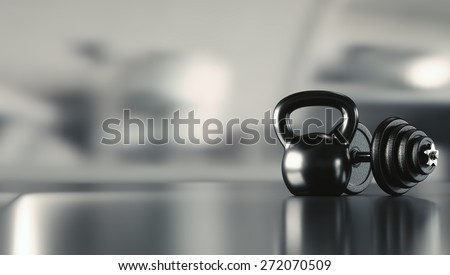 Dumbbell and kettlebell on a reflective floor with space for text. - stock photo