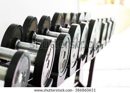 dumbbell exercise weights at gym in the morning - stock photo
