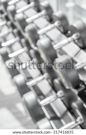 Dumbbell in modern luxury fitness center abstract blur background