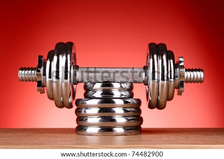Dumbbell on red background - stock photo