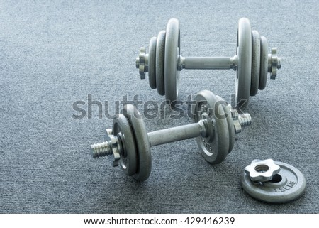 Dumbbell on the gray background - stock photo