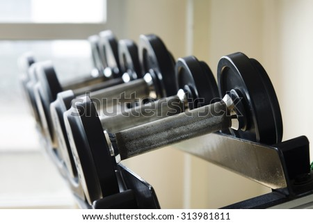 Dumbbell row in fitness room (Selective focus)