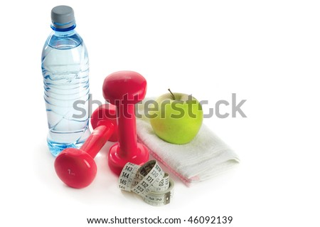 Dumbbells, apple and measuring tape on a white background - stock photo