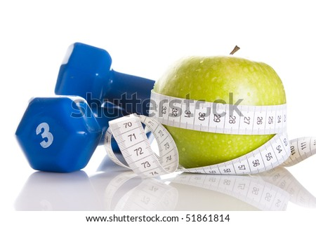 dumbbells, fresh green apple and measure tape - stock photo