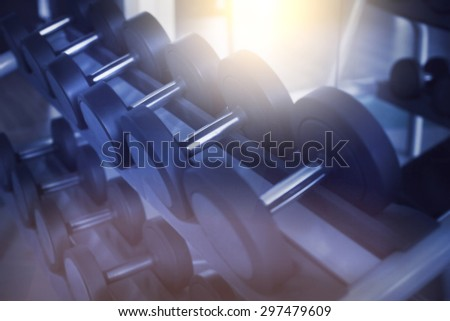 Dumbbells in modern sports club. Weight training equipment. Toned image - stock photo