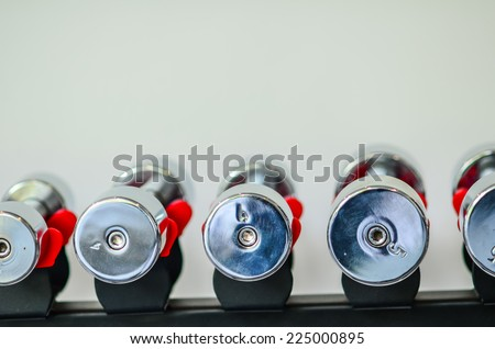 Dumbbells of different scales lie on the sports shelf
