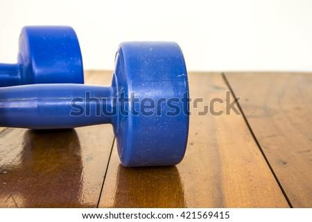Dumbbells on the wooden floor - stock photo