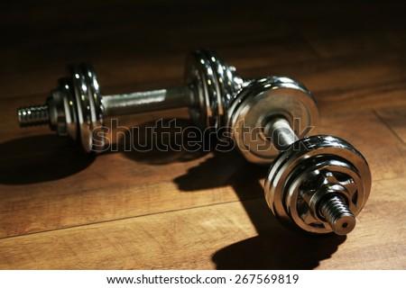 Dumbbells on wooden floor, on dark background - stock photo