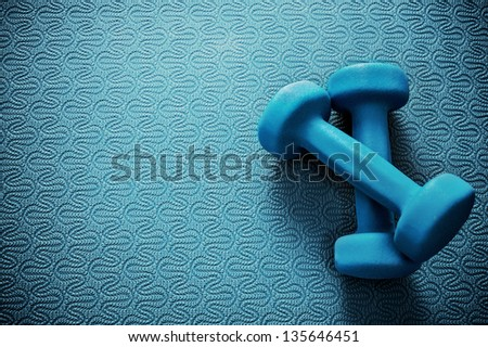 dumbbells on yoga matt - stock photo