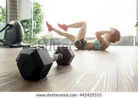 Dumbbells resting on the gym floor with a woman exercising in the background. - stock photo
