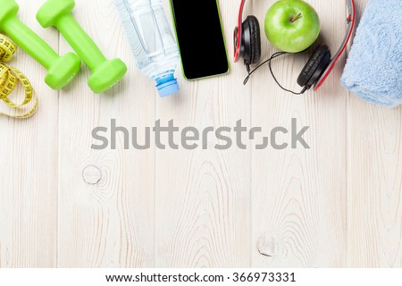 Dumbbells, water bottle, smartphone, headphones and tape measure. Fitness concept. Top view with copy space - stock photo