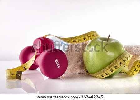 Dumbbells with apple and tape measure on white glass table and isolated background. Concept women lifestyle, health, diet and sports. Horizontal composition. Front view - stock photo