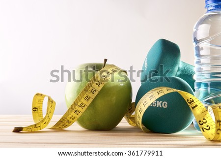 Dumbbells with apple, mineral water bottle and tape measure on wood table and isolated background. Concept lifestyle, health, diet and sports. Horizontal composition. Front view - stock photo