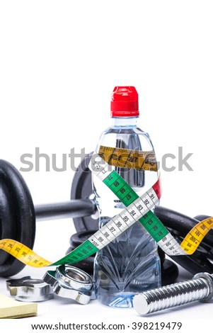 Dumbbells with measuring tape, notepad and bottle of chilling water on white