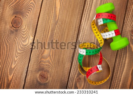Dumbell and tape measure over wooden background. Fitness and health. View from above with copy space - stock photo
