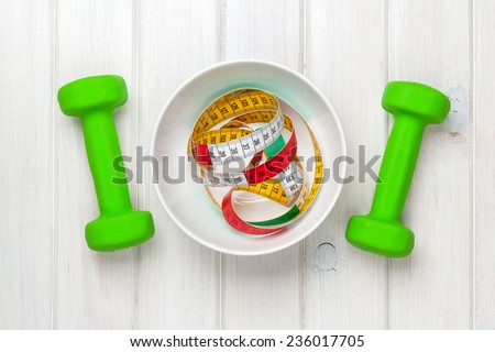 Dumbells and tape measure in bowl over wooden background. Fitness and health. View from above  - stock photo