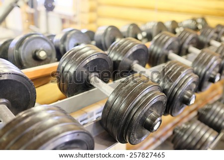 Dumbells in a rack at the gym - stock photo
