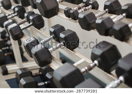 Dumbells on a rack at the gym - stock photo