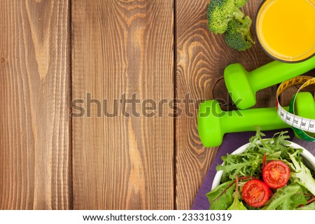Dumbells, tape measure and healthy food over wooden background. Fitness and health. View from above - stock photo