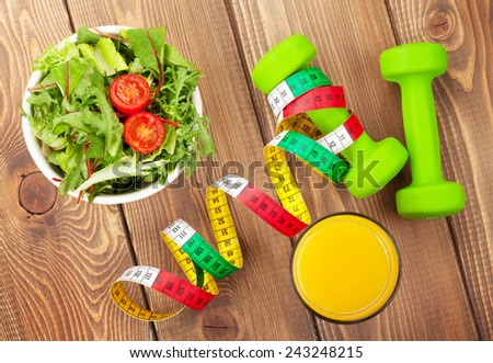 Dumbells, tape measure and healthy food over wooden table. Fitness and health. View from above - stock photo