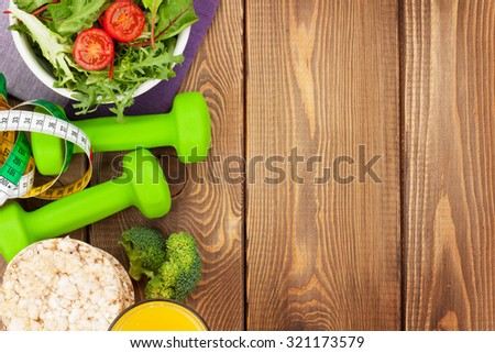 Dumbells, tape measure and healthy food over wooden table with copy space. Fitness and health - stock photo