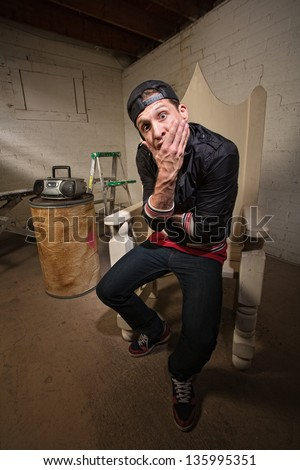 Dumbfounded European rapper sitting on throne holding chin - stock photo