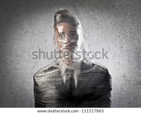 Dummy dressed as a businessman packed in plastic wrap - stock photo