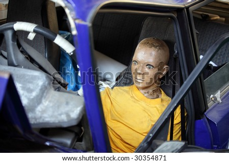 Dummy in the broken car after the test - stock photo