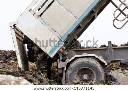 Dump truck dumping soil and dirt in the  construction site