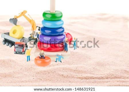 Dump truck, excavator and miniature workers building a pyramid stacking rings structure with sand background - stock photo