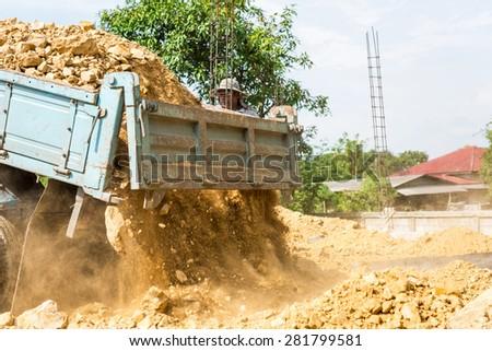 Dump truck unloading soil at construction site - stock photo
