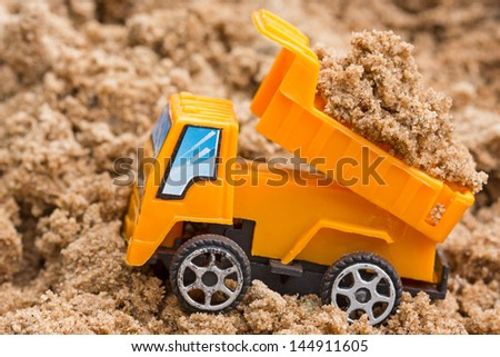 Dump truck unloads soil on the sand at a construction site - stock photo