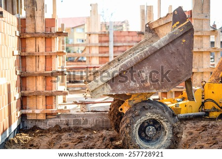 Dumper truck unloading gravel, sand and stones at construction site. Brick layering and working at construction site  - stock photo